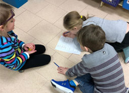 Three elementary students sit on the classroom floor to work on a task together
