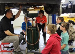 Several elementary students watch as an auto teacher shows them the underside of a car