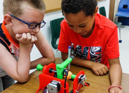 Two elementary stuents work together in a classroom